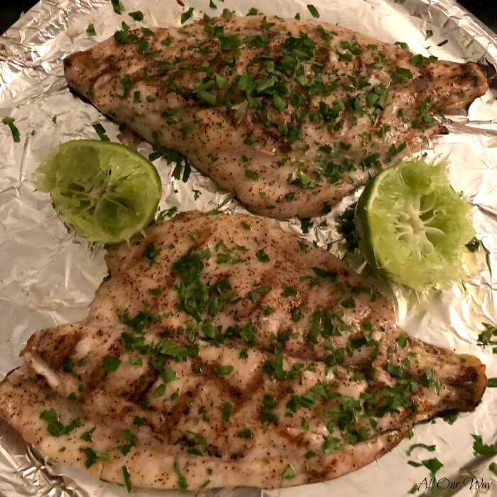 Two Grilled Florida Pompano Fillets on aluminum foiled line baking sheet with 2 lime halves.