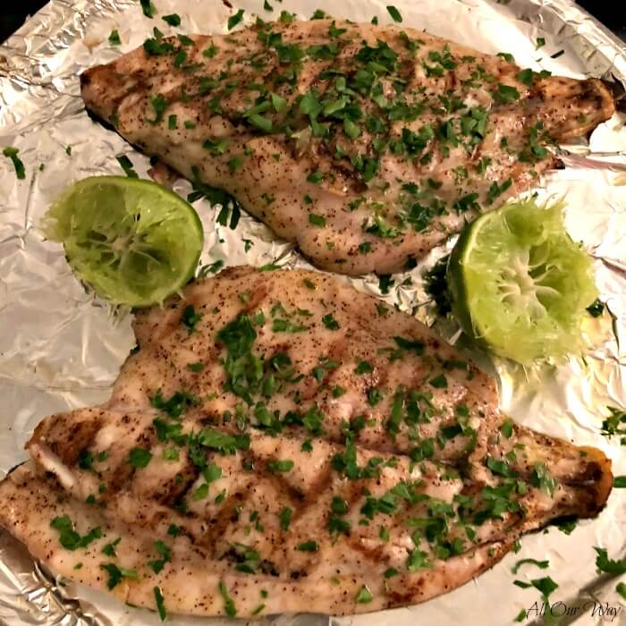 Two Florida Pompano fillets that are grilled on a tray, seasoned with lime and parsley.
