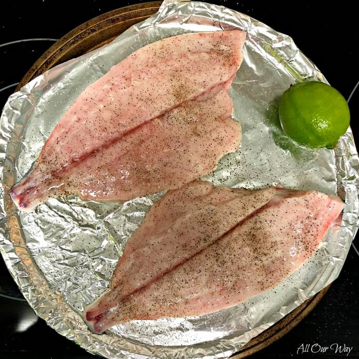 Two Florida Pompano fillets with a lime on a foil lined round baking pan.