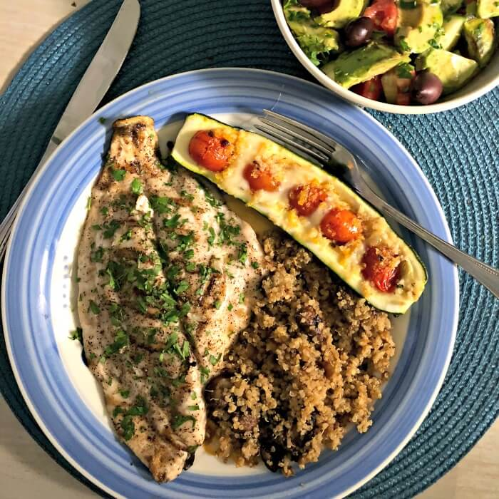 Florida Pompano on a blue rimmed plate with zucchini boats stuffed with tomatoes and quinoa with muchrooms. A salad on the side.