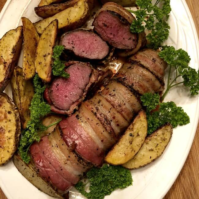 Grilled antelope tenderloin is bacon-wrapped and on white plate with several slices among the baked potato wedges.