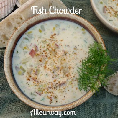 Brown bowl filled with fish chowder with a sprig of green dill on the side and slices of French baguette bread surrounds the bowl.