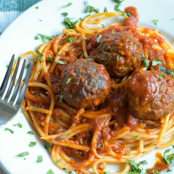 Three baked venison meatballs with spaghetti on a white porcelain plate sprinkled with chopped basil. A fork is on the left side of the plate.