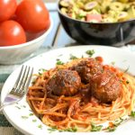 A table set with a white plate with three baked venison meatballs with spaghetti covered in a red sauce. Chopped basil is sprinkled on top. Fork is on left side, a white bowl of red roma tomatoes are behind the plate and next to it is a brown pottery bowl with a tossed salad.