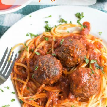 Three baked venison meatballs with spaghetti and red sauce on a white porcelain plate all on top of a green and white checked placemat. A fork rests on the left hand side of the plate.