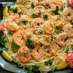 Easy shrimp scampi served over angel hair pasta served on a green platter with lemon slices and pink carnation.