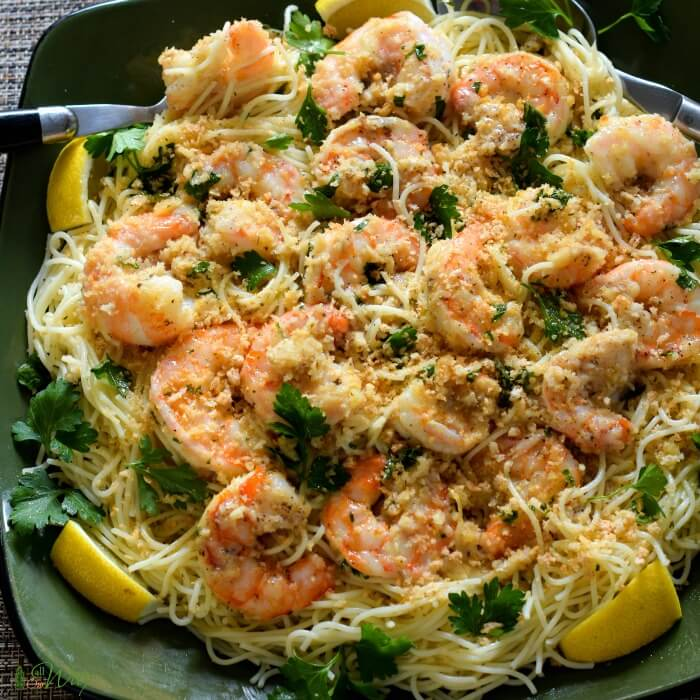 Easy shrimp scampi on top of angel hair pasta with slivers on lemon on a deep green square platter