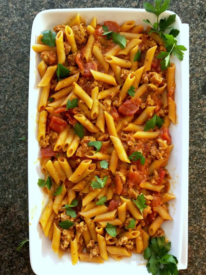 A large white rectangular plate filled with Italian sausage tomato pasta sprinkled with green flat leaf parsley. White platter is on a black and tan speckled marble.