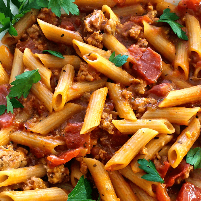 Penne pasta covered with tomato sauce and Italian sausage chunks with a sprinkle of Flat-leaf parsley