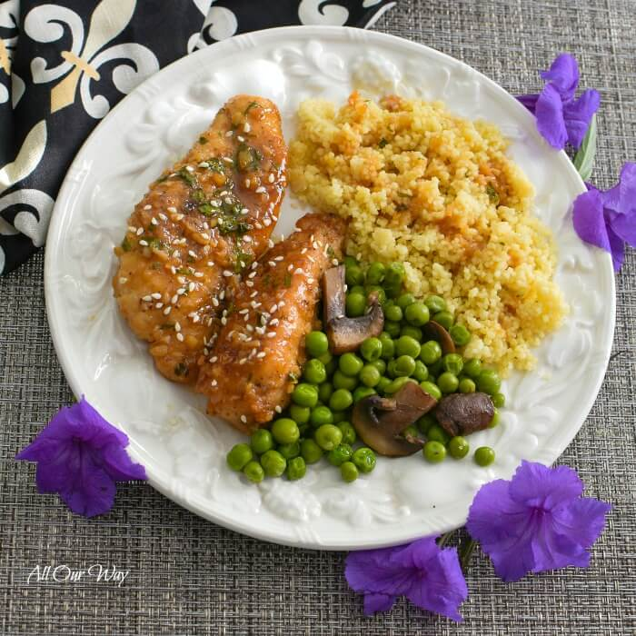 A white plate holds two pieces of honey garlic chicken , green peas with mushrooms, and golden quinoa with honey sauce drizzled on top. Surrounding the plate are 5 purple blossoms and at the upper left hand side is a black napkin with white and gold fleur de lis.
