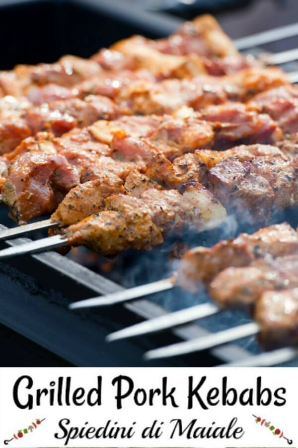 Grilled pork kebabs have chunks of pork are threaded on double prong skewers on a smoking grill.