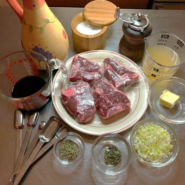 Ingredients for the Balsamic Glazed lamb chops: 4 lamb chops on white plate, balsamic vinegar in cup, olive oil in yellow flowered bottle, sea salt in wooden container, measuring spoons, chicken broth in cup, pat of butter in glass dish, chopped shallots in glass prep bowl, dried rosemary in glass dish, dried time in glass dish.