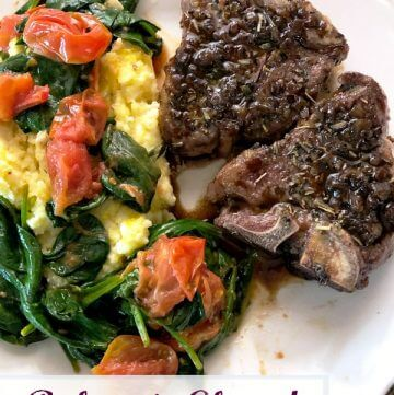 Two browned lamb chops on a white plate with yellow polenta covered with sauteed red grape tomatoes and green baby spinach.