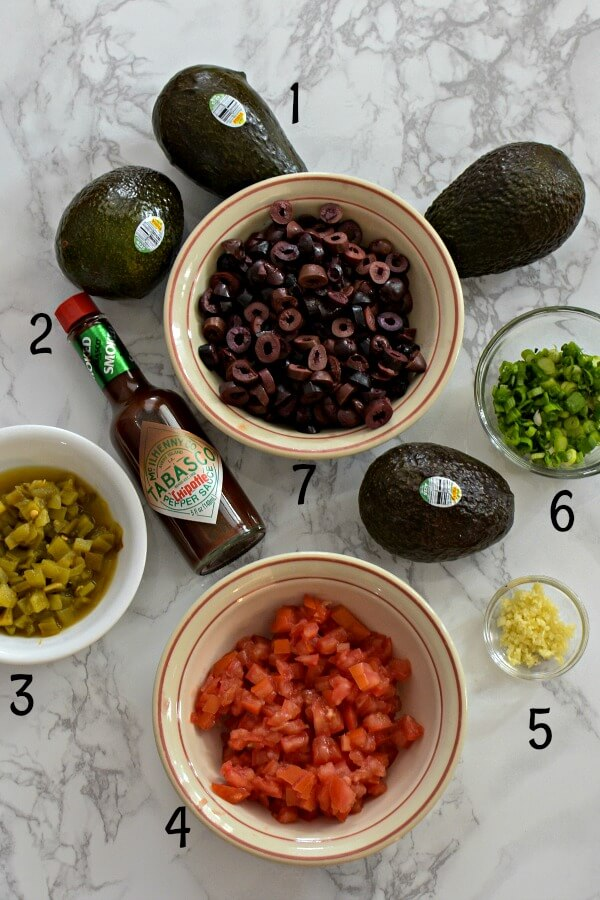 Ingredients for Italian Avocado Salsa on marble, six avocados, TABASCO® Chipotle Sauce, green chilies in white bowl, diced tomatoes in bowl, minced garlic in glass prep dish, chopped green onions in glass, sliced black Kalamata olive in white bowl.