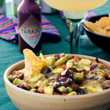 Closeup of tan pottery bowl filled with avocado salsa and a hot sauce bottle in the background with margarita glass filled with lime fruity drink on top of a dark green tablecloth.