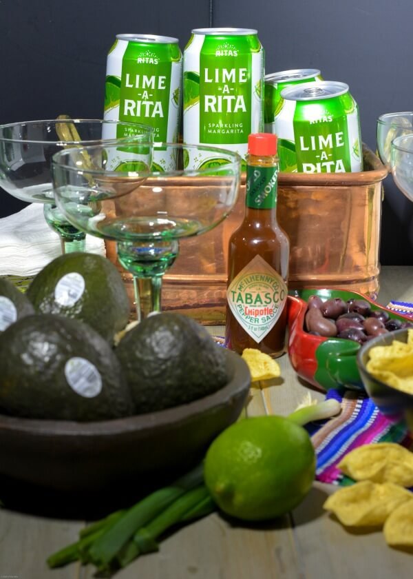Avocados in wooden bowl with lime, TABASCO®Sauce, green and white aluminum Lime-A-Rita cans in copper tub with green margarita glasses and tortilla chips on table.