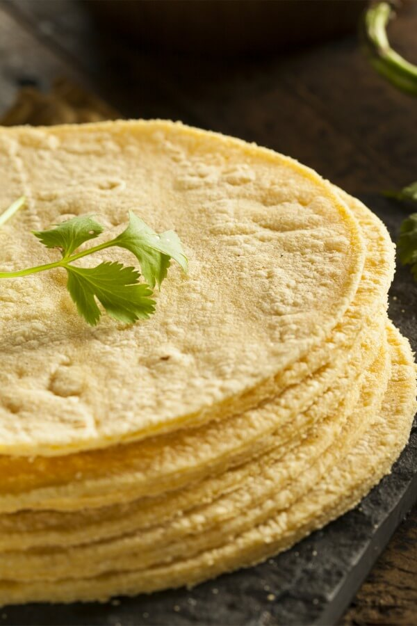 Stack of corn tortillas on a dark table with a green cilantro stem on top.