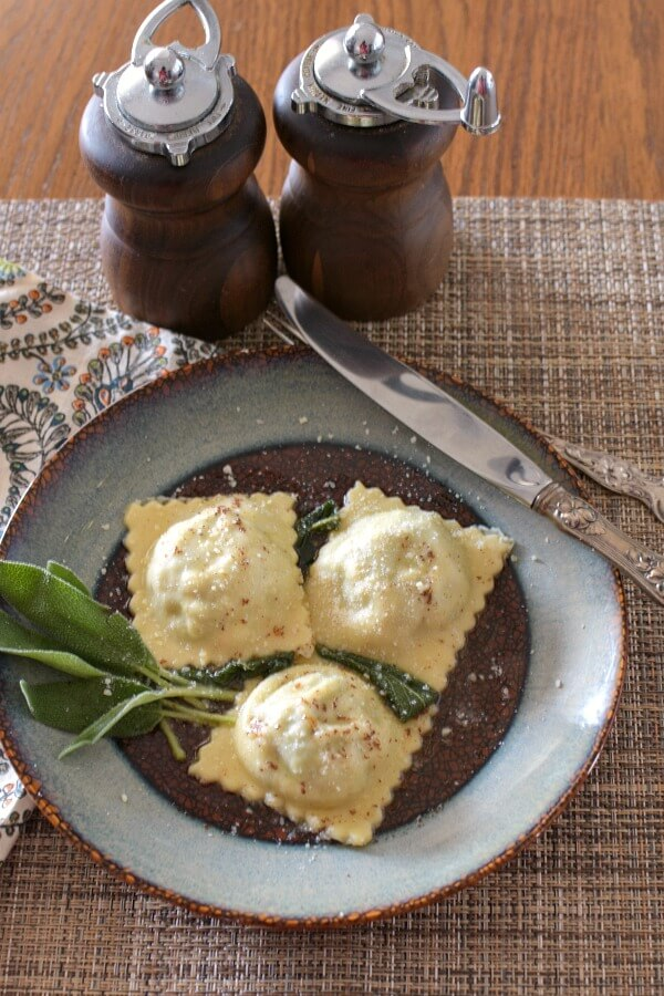 Three lamb ravioli with sage sprig on a brown plate with blue trim and wooden salt and pepper grinders next to plate.