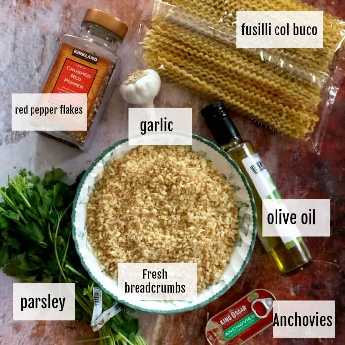 Overhead view of the ingredients for Fusilli Col Buco With Toasted breadcrumbs including, hot pepper flakes, parsley, garlic, fusilli pasta, olive oil, and a tin of anchovies.