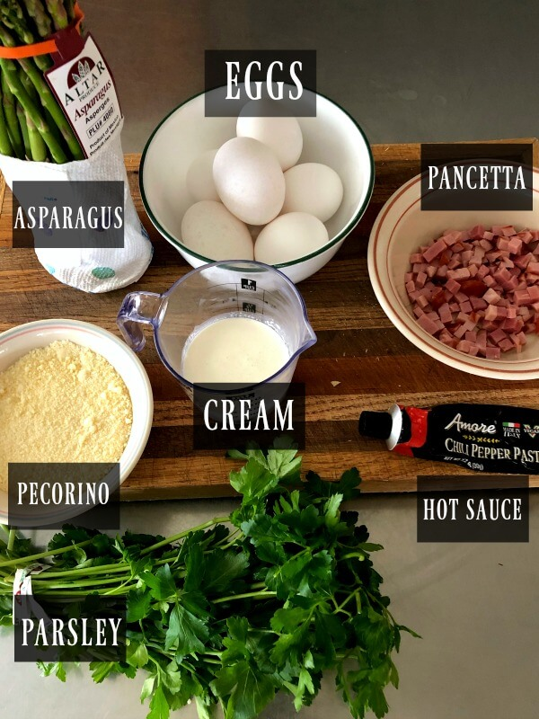 An overhead shot of a frittata ingredients, eggs, prociutto, asparagus, pecorino-romano cheese, cream, hot sauce paste, parsley.