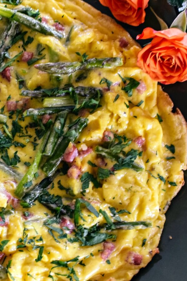 Asparagus frittata on a green platter with a coral rose flowers on the upper right.