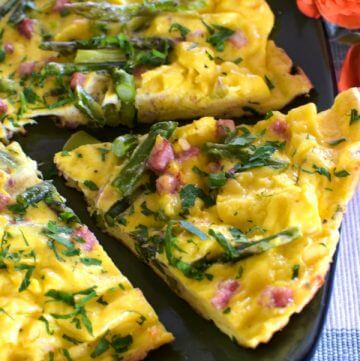 Close up of an asparagus frittata on a green plate with a slice cut. Coral roses on the right side.
