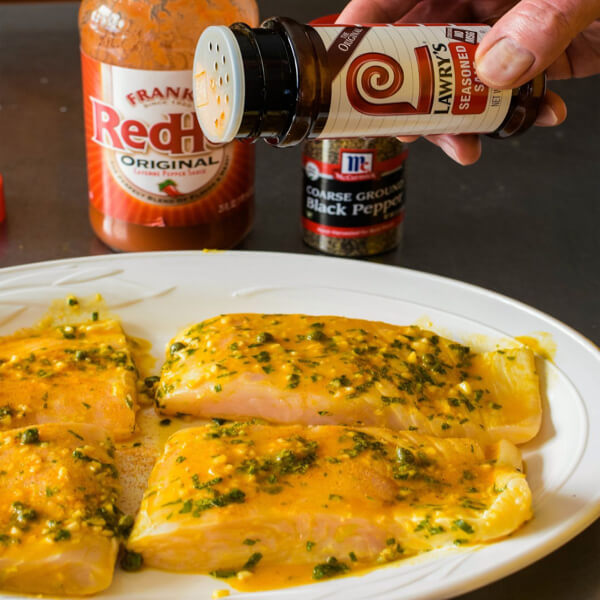 Four halibut fillets on a platter being seasoned with Lawry's®Seasoned Salt and hot sauce and pepper in the background.