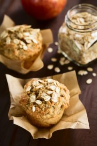 Two oatmeal muffins on brown parchment square with red apple and glass canister of oatmeal