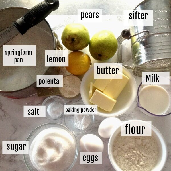 All the ingredients necessary to make the polenta cake including flour, cornmeal, lemon, eggs, pears, salt, sugar, milk, butter, baking powder plus a springform pan and flour sifter.