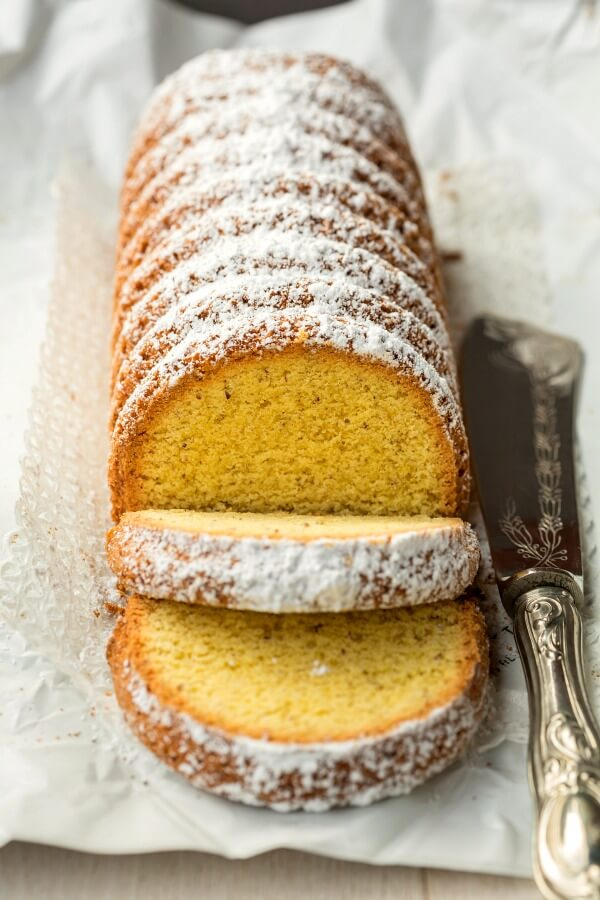 A long tube-like Polenta cake with white powdered sugar on top of a platter with silver serving knife on side.