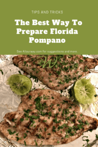 Two pompano fish fillets with grill marks and two lime halves on foil lined round baking tray .