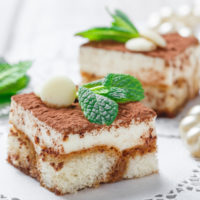 Two square pieces of tiramisu cake on a white plate with mint leaves on top.