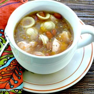 White soup bowl filled with pasta, beans, and chicken on a white plate and russet napkin on side.
