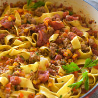 Red brassiere filled with pappardelle pasta tossed with sausage, colored bell peppers, and tomatoes, A parsley leaf on top.