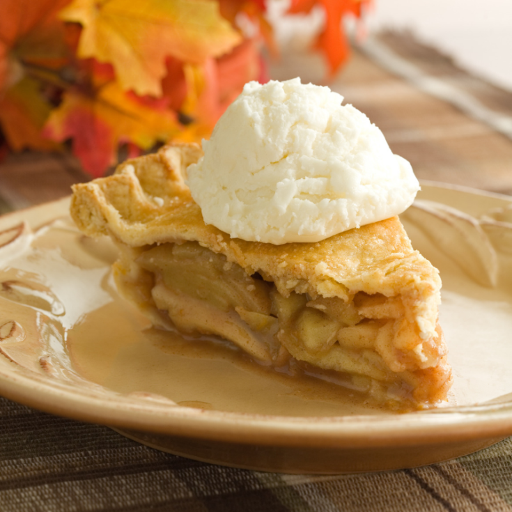 Apple pie slice on tan plate with a scoop of ice cream on top. Autumn colored leaves in the background.