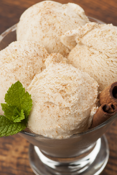 Four scoops cinnamon ice cream in a glass goblet with mint and cinnamon stick on top.