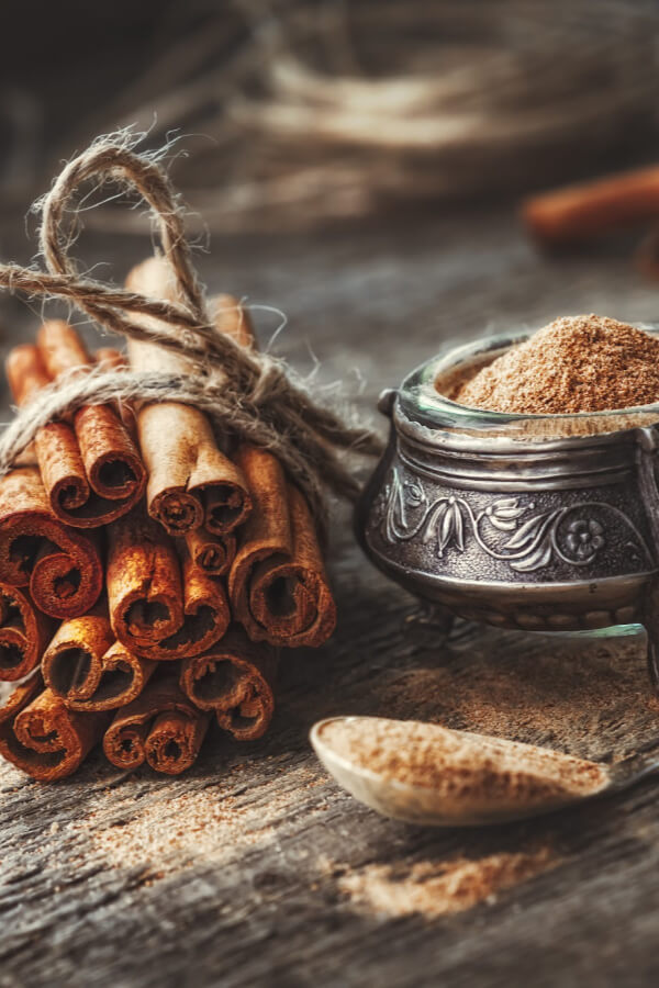 Cinnamon sticks tied together with jute cord and ground cinnamon on wooden table along with pewter bowl filled with the spice.