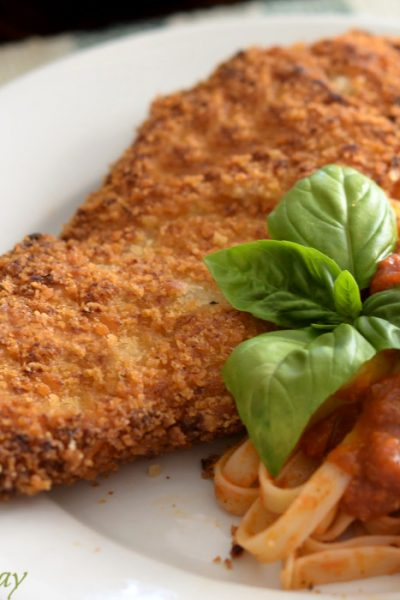 Golden brown Chicken cutlets on white plate with pasta covered in tomato sauce and a basil sprig.
