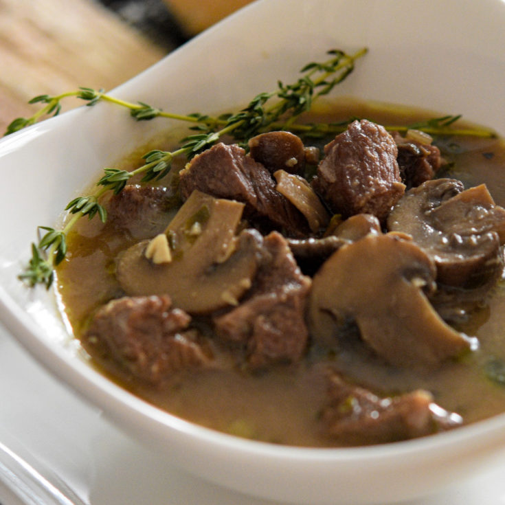 Roasted Mushroom steak soup with chunks of meat and mushrooms in broth in white triangular bowl.