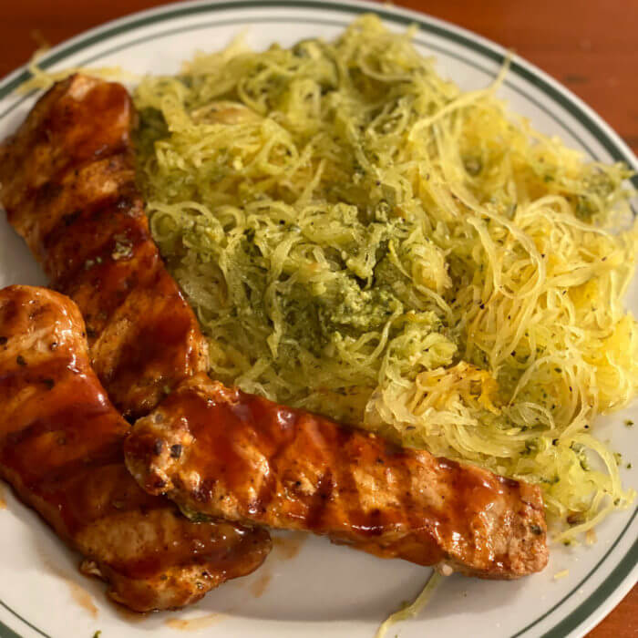 Grilled barbecue pork strips with roasted spaghetti squash tossed with pesto on a white plate.