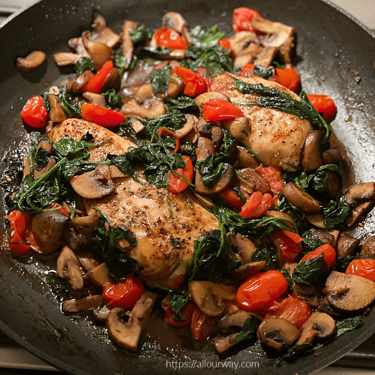 Two Chicken Breasts Florentine in large skillet with spinach and grape tomatoes, mushrooms.