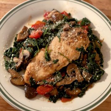 Chicken Florentine on Green edged plate with spinach, tomatoes, and mushroorms.