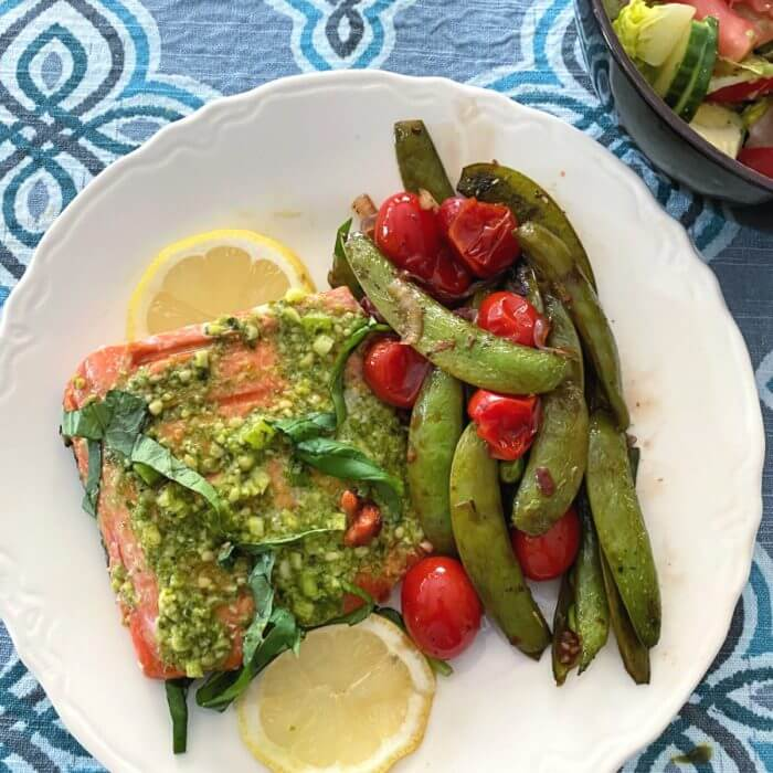 Sugar snap peas on white plate with roasted salmon and sliced lemons
