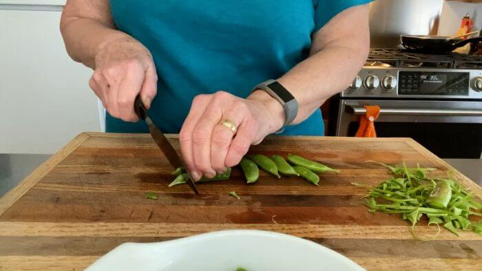 Cutting and trimming sugar snap peas on cutting board.
