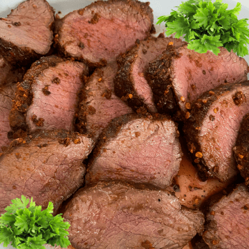 Grilled venison backstrap sliced with parsley on side.
