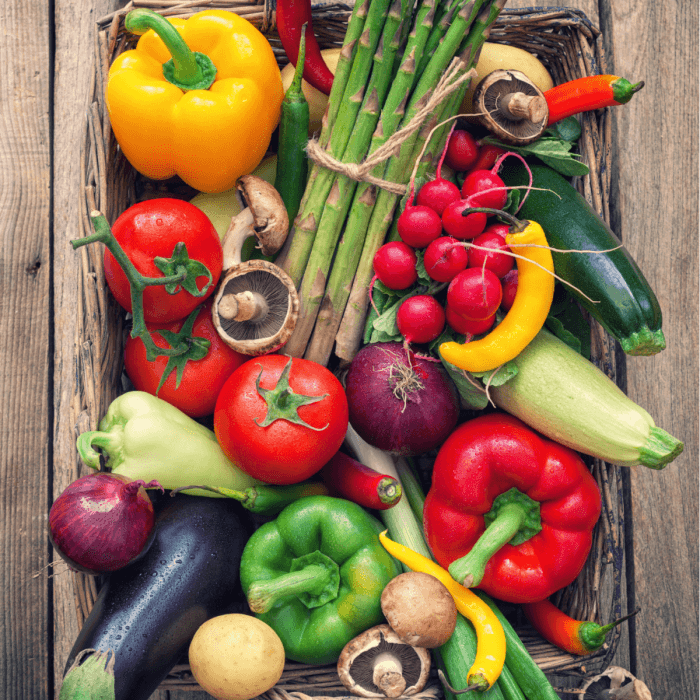 A basketful of vegetables such as colored bell peppers, mushrooms, purple onion, zucchini, tomatoes and more.