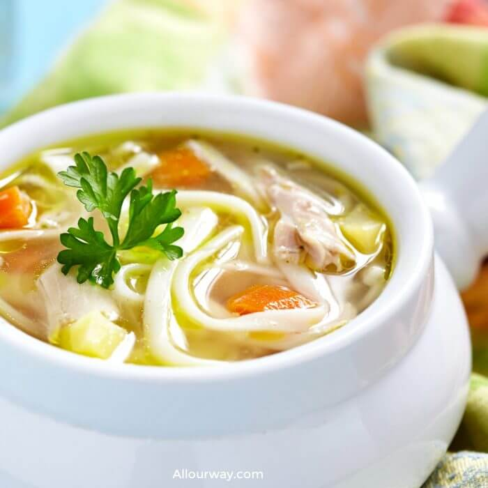 White bowl filled with homemade chicken soup with noodles and carrots and celery.