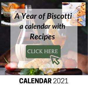 Photo of Chianti bottle with a glass of wine and biscotti.
