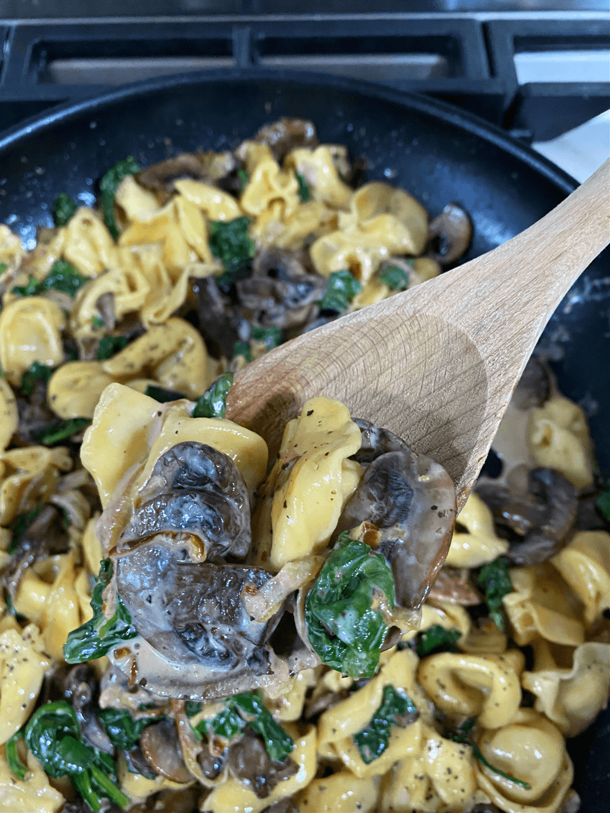 A wooden spoon filled with cheese tortellini, caramelized onions, spinach and mushrooms.