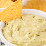 Creamy Guacamole Salsa in a white bowl with a tortilla chip ready for dipping.